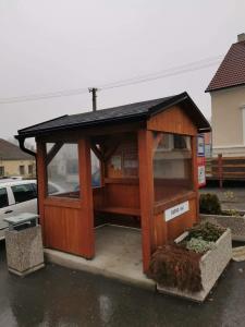 dřevěná autobusová zastávka se sedlovou střechou